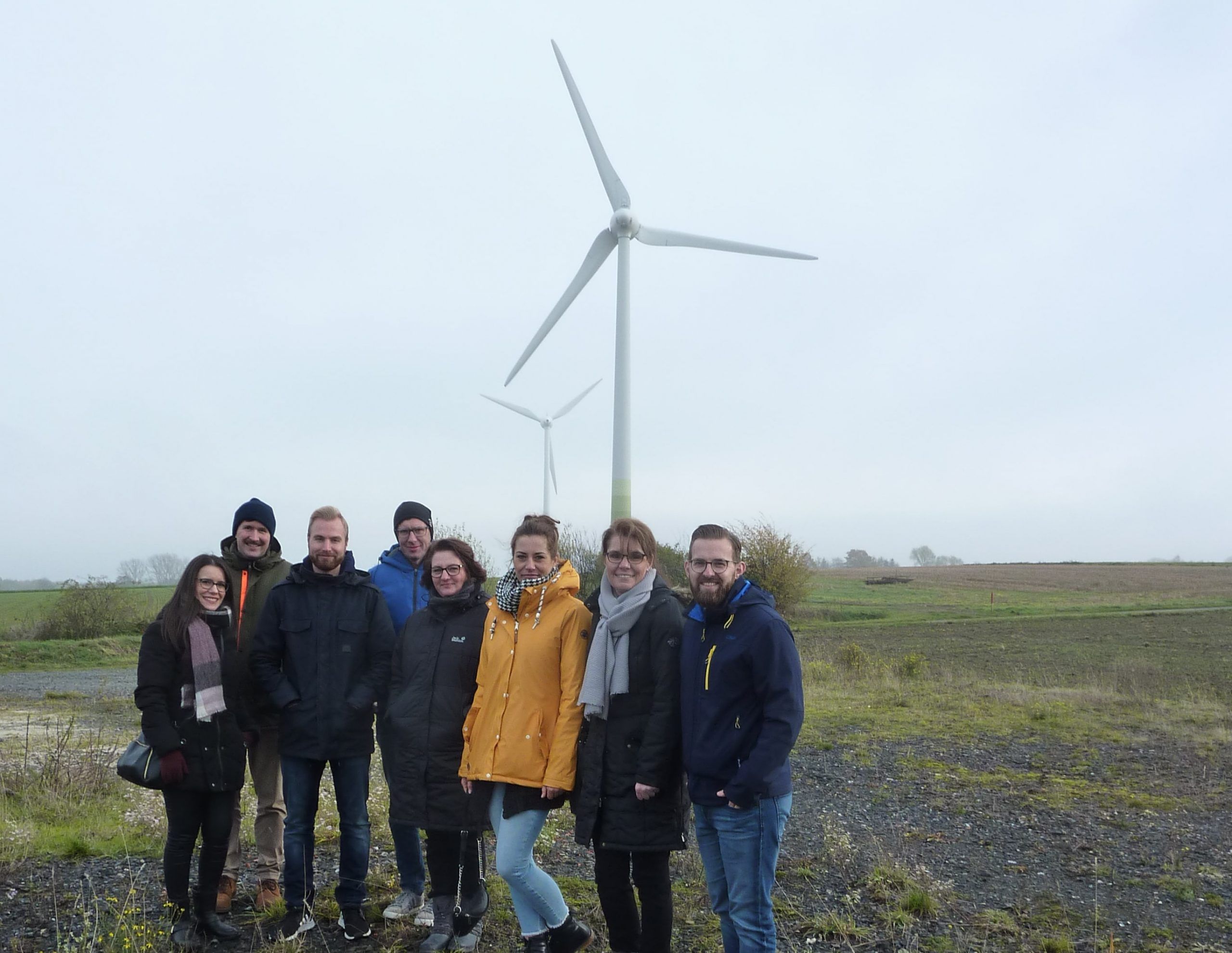 Mitarbeiter der Abteilung Erneuerbare Energien vor Windrädern