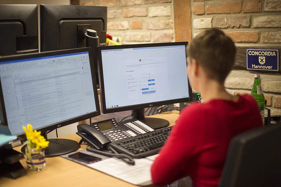 Frau vor Computerbildschirmen im Büro