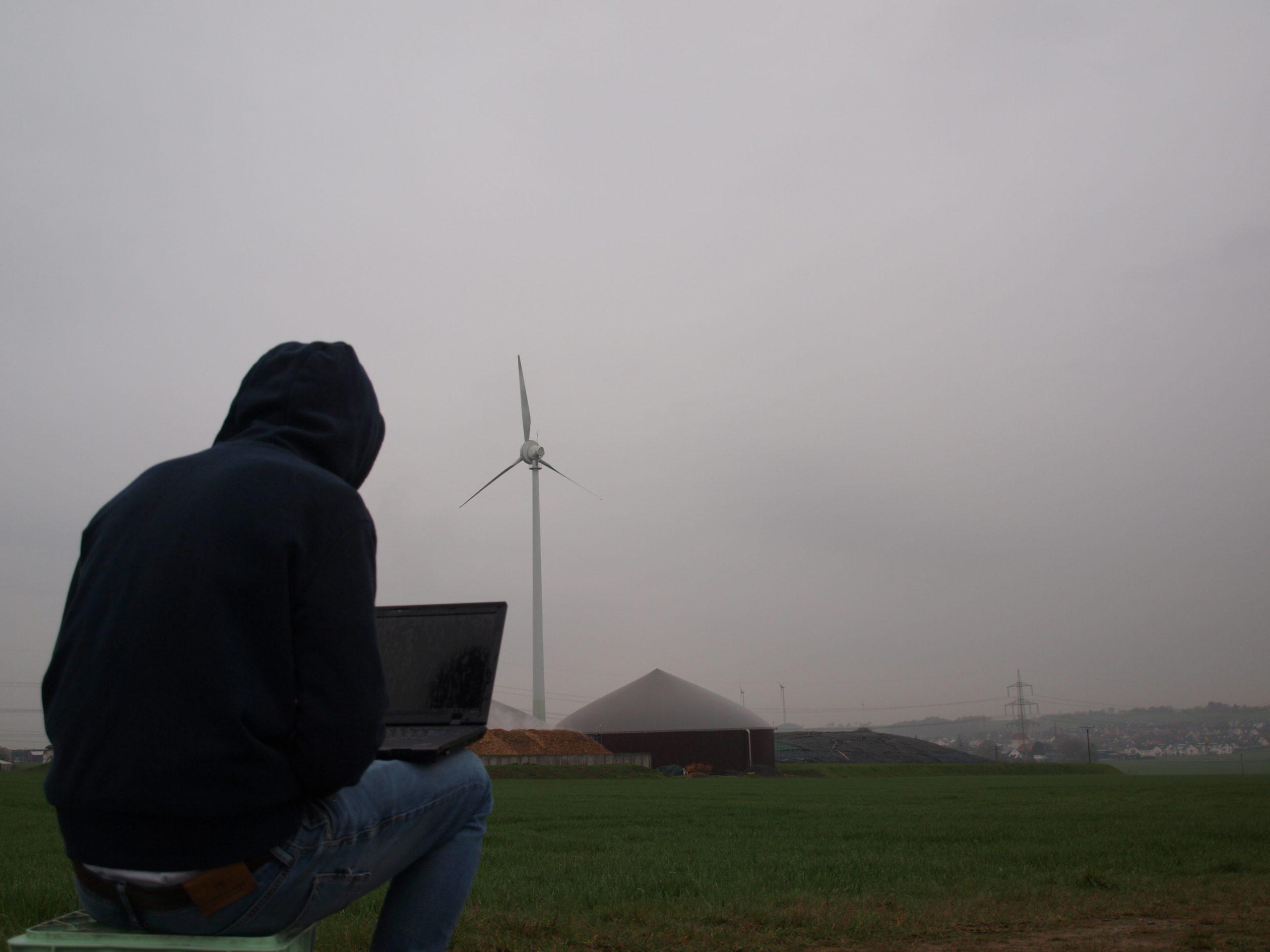 Hacker vor Windrad mit Laptop
