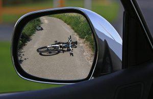 Blick durch Auto-Außenspiegel auf auf der Straße liegendes Fahrrad