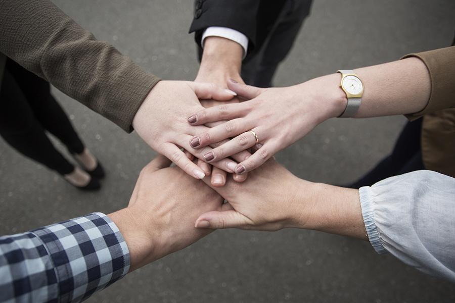 Hände der Mitarbeiter übereinander