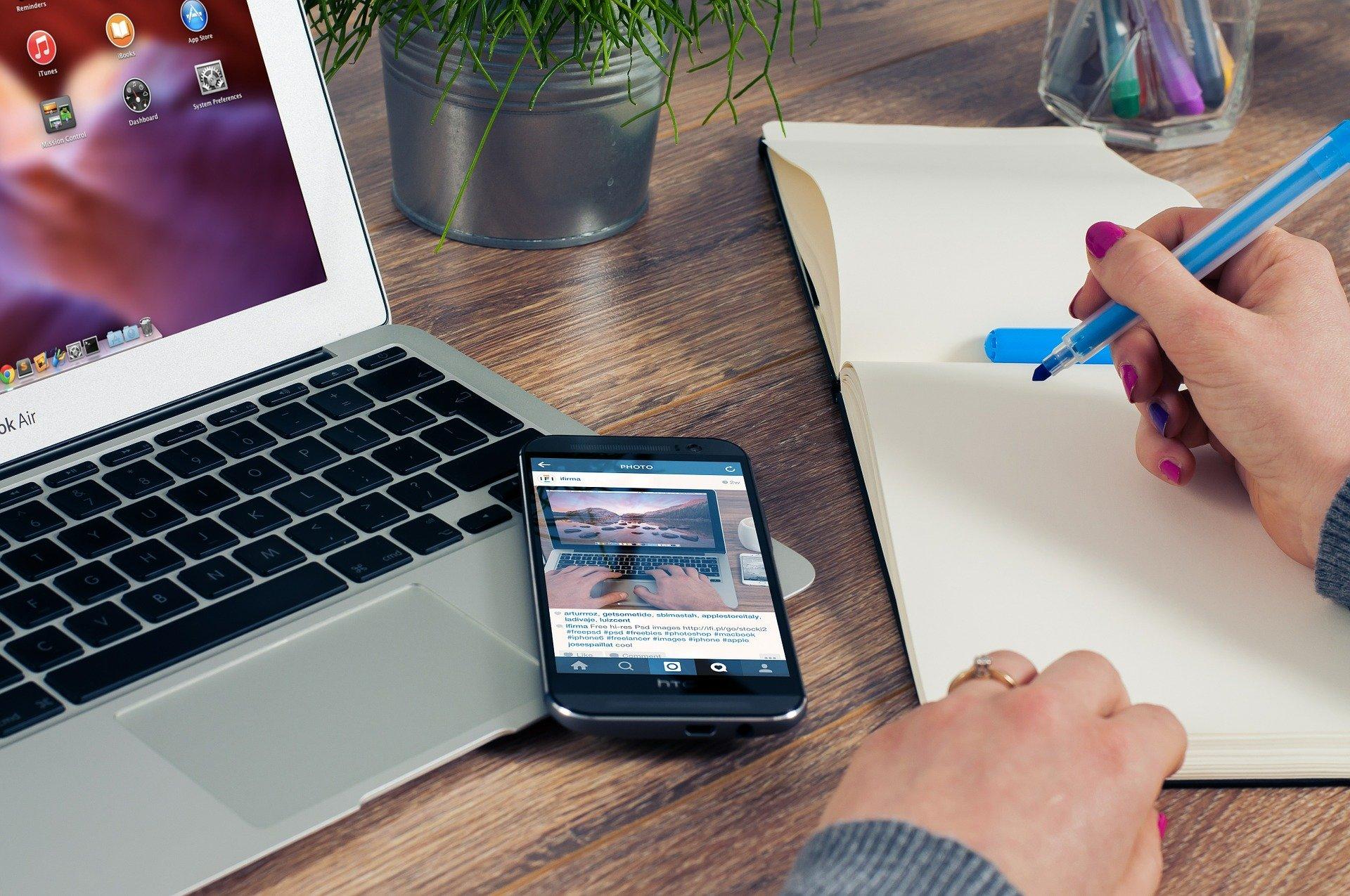 Home Office Arbeitsplatz mit Laptop, Smartphone und Notizblock