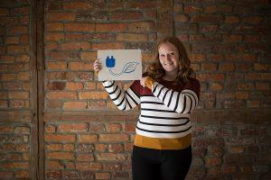 Mitarbeiterin mit Schild zum Thema Nachhaltigkeit